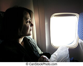 Air traveler - Young woman side lit by the veiw from her...