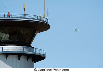 Airbase tower and F-16 jetfighter flyby