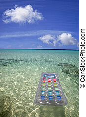 Airbed in the Sea - Airbed floating in green lagoon water...