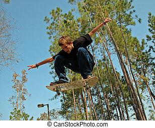 A teenaged skateboarder soars through the air on his skateboard at a suburban skate park