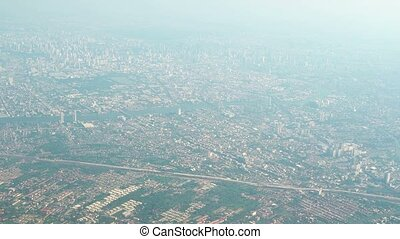 """Airborne View of a Sprawling, Asian Cityscape on a Foggy..."