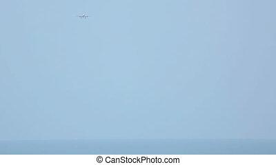 Airbus 330 approaching over ocean before landing in...
