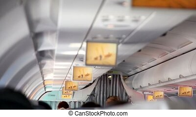 Aircraft cabin, under ceiling hung displays and show extrime...