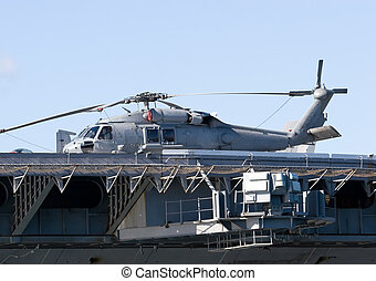Aircraft Carrier - A navy helicopterr on the deck of an...