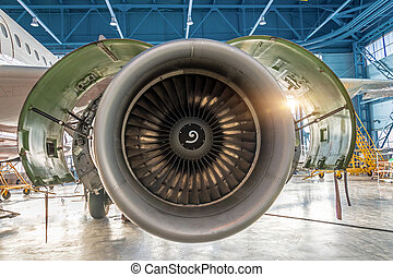 Aircraft engine jet with open hood on the sides in the hangar for maintenance