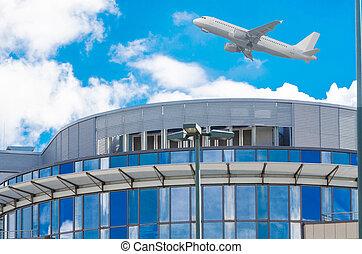 Aircraft flies over office building.