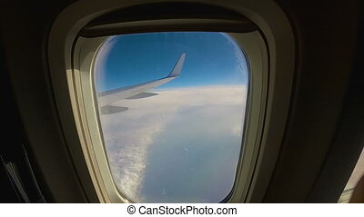 aircraft flies over the clouds, view through the window to the wing of an passenger airplane