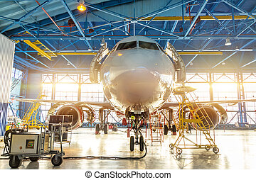 Aircraft in the aviation industrial hangar on maintenance, outside the gate bright light.