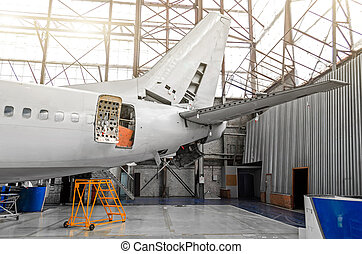 Aircraft in the hangar in the maintenance of plating, interior, tail repair.