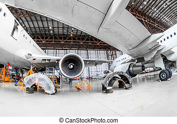 Aircraft in the hangar repair and maintenance, view from under the wing of the airplane.