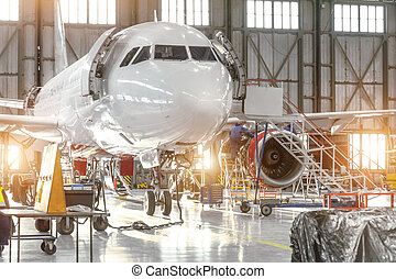 Aircraft jet on maintenance of engine and fuselage check repair in airport hangar.