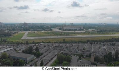 Aircraft landing strip empty old aircraft factory plant aerial drone view rises up camera movement