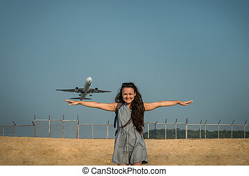 Aircraft like a bird. Jet plane takes off on the background behind a young woman