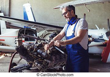 Aircraft maintenance mechanic inspects plane engine