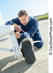 aircraft mechanic checking landing gear