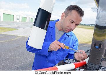 aircraft mechanic fixing the problem