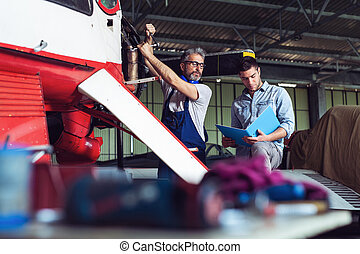 Aircraft mechanics in the hangar. Coworkers repairing an aircraft
