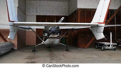 Private aircraft parked at hangar 4k
