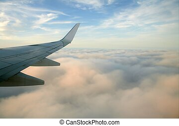 Aircraft right side wing, airplane flying over clouds in a blue sky