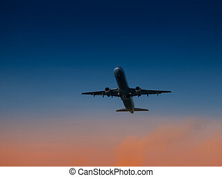 Aircraft take-off from airport at sunset time. Air transportation and overnight flight theme