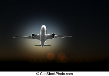 Aircraft taking off on dark sky with lights from airport in...