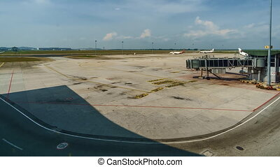 Aircraft taxiing at KLIA with service vehicles in the foreground. Time lapse