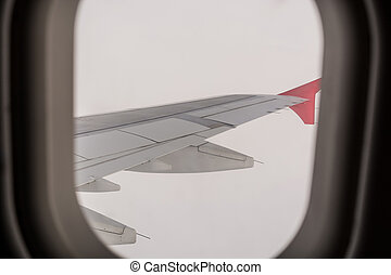 Aircraft windows overlooking the wing of the aircraft.