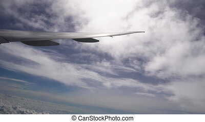 Aircraft wing between layers of white clouds high in the sky at sunny weather