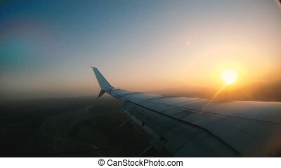 Aircraft wing flaps. The plane flies and is seen through the porthole dawn