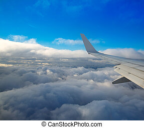 Aircraft wing flying onver a sea of clouds