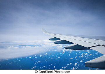 Aircraft wing flying over clouds.