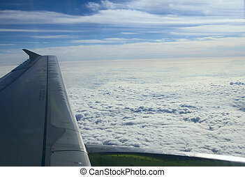 Aircraft wing on a background of clouds from the window. Blue sky, white clouds and city below.