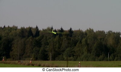 View of glider landing on forest background