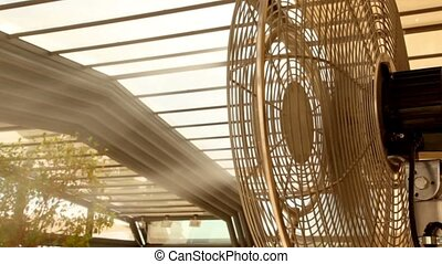 Airflow from the fan atomizes a jet of water on plants, fan...