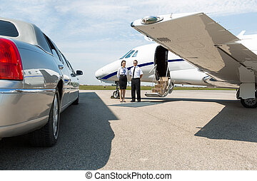 Airhostess And Pilot Standing Neat Limousine And Private Jet...