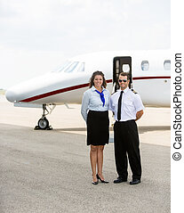 Airhostess And Pilot Standing Together Against Private Jet