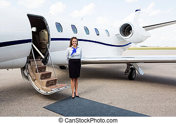 Airhostess Standing By Private Jet - Full length portrait of...