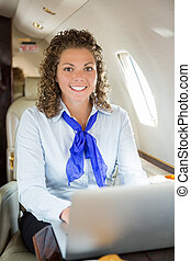 Airhostess With Laptop In Private Jet