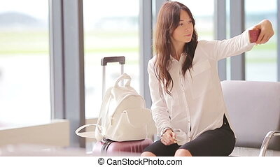 Airline passenger in an airport lounge waiting for flight aircraft and making selfie. Caucasian woman with smartphone in the waiting room
