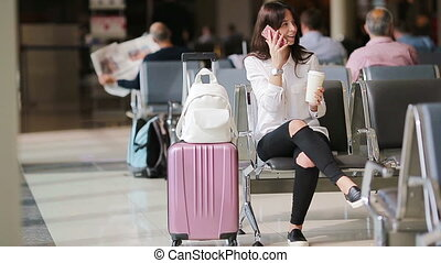 Airline passenger in an airport lounge waiting for flight aircraft. Caucasian woman looking for time in the waiting room
