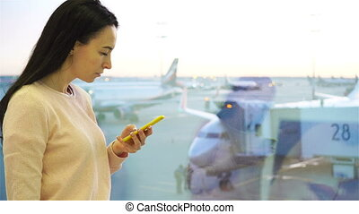 Airline passenger in an airport lounge waiting for flight aircraft. Caucasian woman talk by cellphone near big window background the big plane