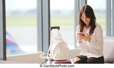 Airline passenger in an airport lounge waiting for flight aircraft. Caucasian woman with smartphone in the waiting room