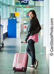 Airline passenger with baggage in an airport lounge waiting for flight aircraft. Young woman in international airport, walking with her luggage