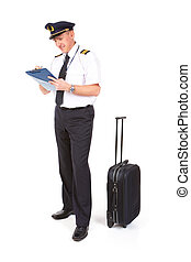 Airline pilot wearing hat, shirt with epaulets and tie filling in and checking papers flight plan and weather forecast his trolley is standing near by.