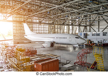 Airliner aircraft in a hangar with an open gate to the service.