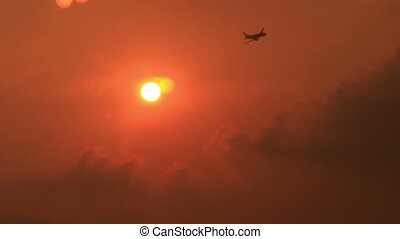Airliner Flies above Clouds against Sun Disk at Sunset -...