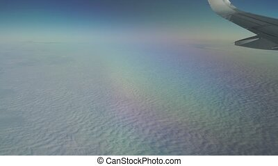 Airliner flying high above the clouds. Porthole view, aerial...