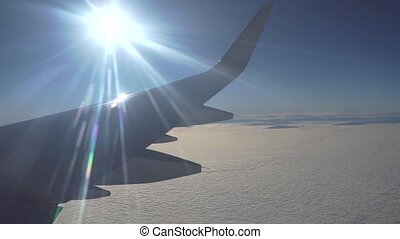 Airliner flying high above the clouds. View from porthole...