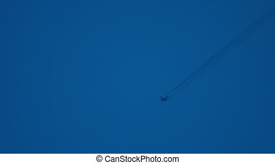 Airliner flying high - Contrails in the evening sky....