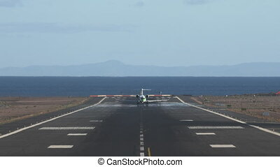 Airliner taking off. Scenic runway overlooking sea and mountains